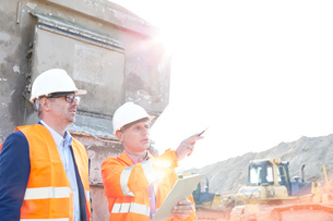 Supervisor showing something to colleague at construction site on sunny dayの写真素材 [FYI03656936]