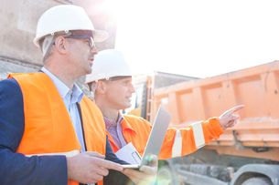 Supervisor showing something to colleague holding laptop at construction siteの写真素材 [FYI03656940]