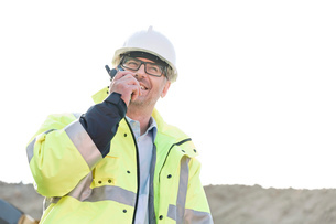 Happy supervisor using walkie-talkie at construction site against clear skyの写真素材 [FYI03656948]