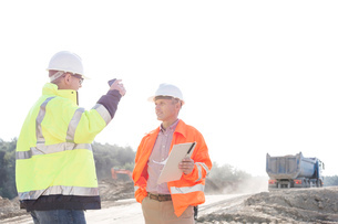 Supervisors discussing at construction site against clear skyの写真素材 [FYI03656963]