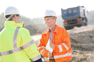 Happy engineer discussing with colleague at construction site on sunny dayの写真素材 [FYI03656967]