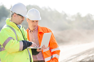 Supervisors using laptop at construction siteの写真素材 [FYI03656970]