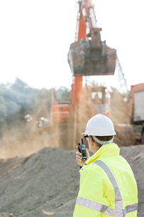 Side view of engineer using walkie-talkie at construction siteの写真素材 [FYI03656974]
