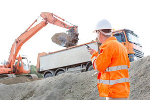 Side view of architect using walkie-talkie while working at construction siteの写真素材 [FYI03656976]