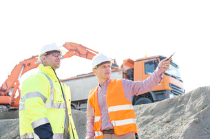 Engineer showing something to colleague while discussing at construction site against clear skyの写真素材 [FYI03656977]