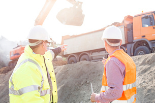 Engineer pointing at vehicles while discussing at construction siteの写真素材 [FYI03656978]
