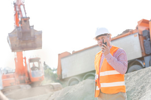 Architect using walkie-talkie while working at construction siteの写真素材 [FYI03656979]