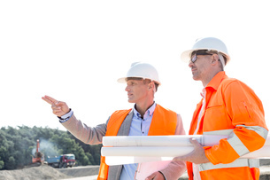 Male engineers discussing at construction site against clear skyの写真素材 [FYI03656983]