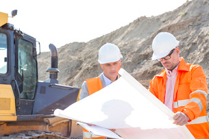 Engineers analyzing blueprint at construction siteの写真素材 [FYI03656987]