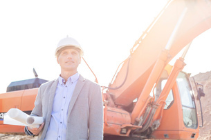 Thoughtful engineer looking away while holding blueprints by bulldozer at construction siteの写真素材 [FYI03656990]