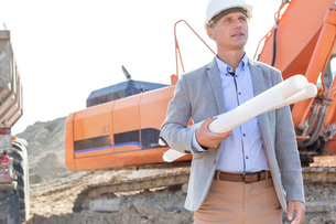 Confident architect looking away while holding blueprints at construction siteの写真素材 [FYI03656993]