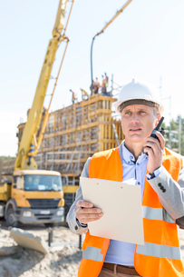 Male supervisor using walkie-talkie while holding clipboard at construction siteの写真素材 [FYI03656998]