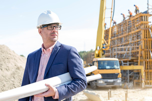 Confident architect holding rolled up blueprints at construction siteの写真素材 [FYI03656999]