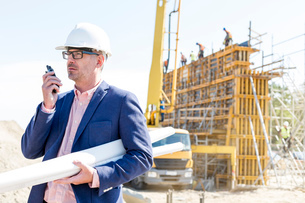 Architect using walkie-talkie while holding blueprints at construction siteの写真素材 [FYI03657000]