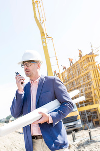 Supervisor using walkie-talkie while holding blueprints at construction siteの写真素材 [FYI03657001]