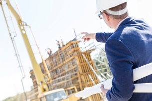Rear view of architect holding blueprints while pointing at construction siteの写真素材 [FYI03657004]
