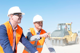 Supervisor explaining plan to colleague at construction site against clear skyの写真素材 [FYI03657005]