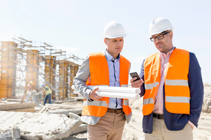 Male engineers using mobile phone at construction site against clear skyの写真素材 [FYI03657008]