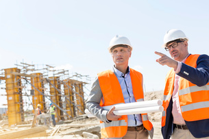 Male engineers discussing at construction site against clear skyの写真素材 [FYI03657009]