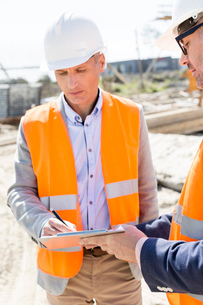 Engineers writing on clipboard at construction siteの写真素材 [FYI03657011]
