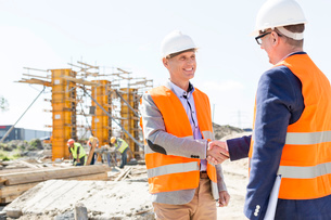 Engineers shaking hands at construction site against clear skyの写真素材 [FYI03657012]