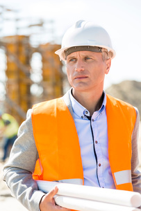 Thoughtful architect looking away while holding blueprints at construction siteの写真素材 [FYI03657013]