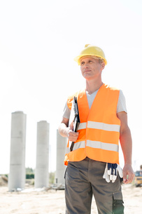 Thoughtful architect looking away while holding clipboard at construction siteの写真素材 [FYI03657018]