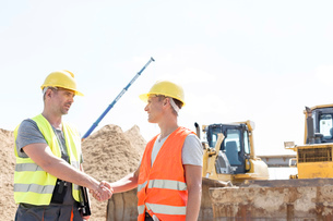 Architects shaking hands at construction site against clear skyの写真素材 [FYI03657031]