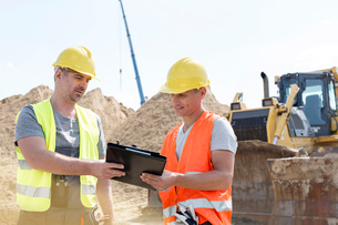 Engineers reading clipboard at construction site against clear skyの写真素材 [FYI03657032]