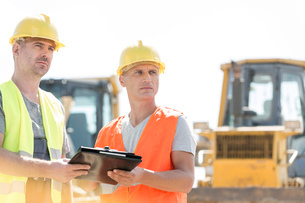Engineers looking away while holding clipboard at construction site against clear skyの写真素材 [FYI03657033]