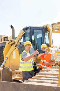 Engineers pointing while discussing at construction site against clear skyの写真素材 [FYI03657034]