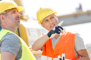 Supervisor showing something to colleague at construction site on sunny dayの写真素材 [FYI03657036]