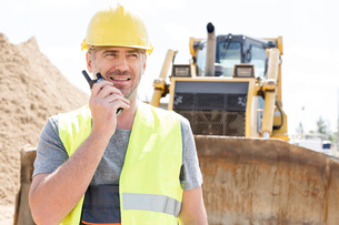 Confident supervisor using walkie-talkie at construction siteの写真素材 [FYI03657038]
