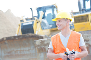 Smiling supervisor looking away at construction siteの写真素材 [FYI03657042]