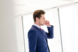Side view of young businessman using mobile phone in new officeの写真素材 [FYI03657047]