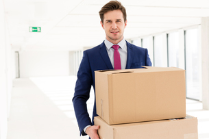 Portrait of young businessman carrying cardboard boxes in new officeの写真素材 [FYI03657060]
