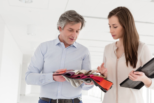 Businesswoman and businessman discussing over cloth swatches in new officeの写真素材 [FYI03657097]