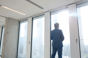 Rear view of mature businessman looking through office windowの写真素材 [FYI03657115]