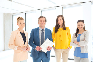 Portrait of mature businessman with female colleagues in new officeの写真素材 [FYI03657147]