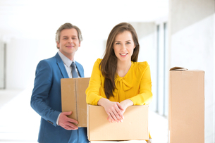 Portrait of confident businesswoman and male colleague with cardboard boxes in new officeの写真素材 [FYI03657171]