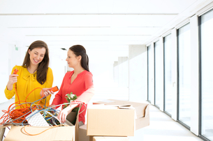 Businesswomen untangling cords while standing by cardboard boxes in new officeの写真素材 [FYI03657175]