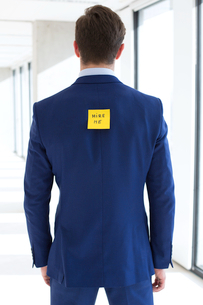 Rear view of young businessman with hire me adhesive note at officeの写真素材 [FYI03657179]