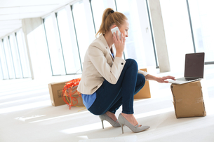 Side view of young businesswoman crouching while using mobile phone and laptop in new officeの写真素材 [FYI03657189]