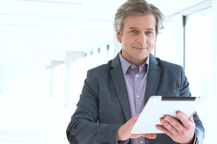 Portrait of mature businessman using digital tablet in new officeの写真素材 [FYI03657204]