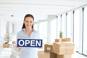 Portrait of smiling businesswoman holding open sign in new officeの写真素材 [FYI03657205]