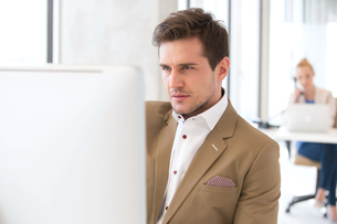 Handsome young businessman using computer in officeの写真素材 [FYI03657219]
