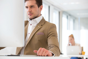 Handsome young businessman using computer in office with female colleague in backgroundの写真素材 [FYI03657225]