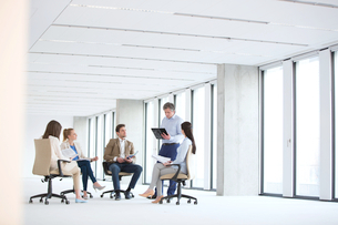 Mature businessman having discussion with team on chair in new officeの写真素材 [FYI03657248]