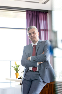 Portrait of mature businessman with arms crossed leaning on desk in officeの写真素材 [FYI03657256]
