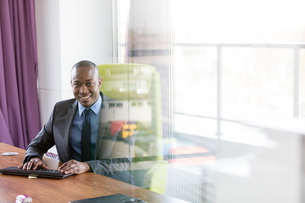 Portrait of smiling young businessman using computer keyboard at desk in officeの写真素材 [FYI03657258]